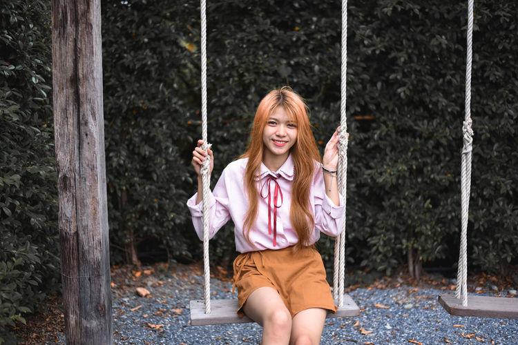 Woman sitting on swing at playground