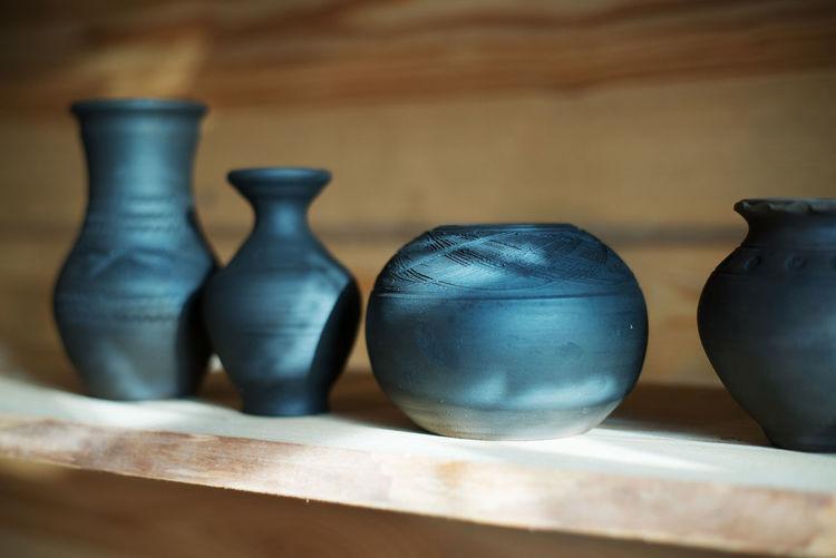 Close-Up Of Pots On Shelf At Workshop