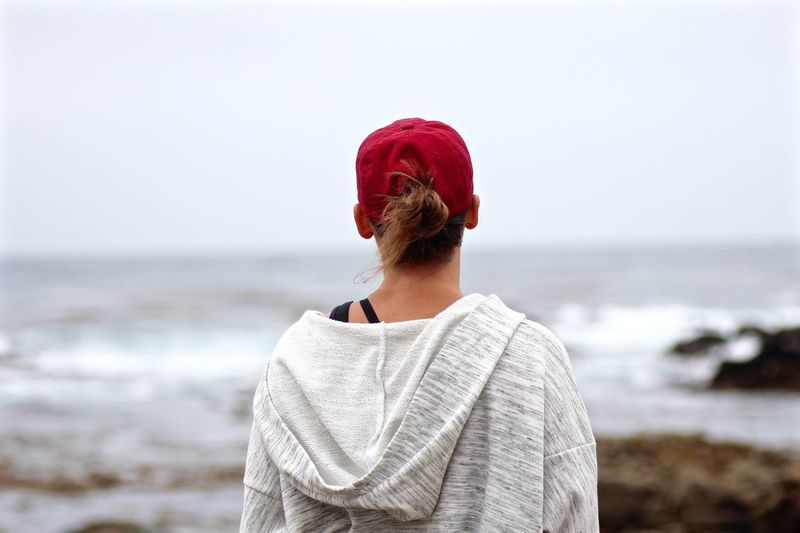 Rear view of woman in cap at beach against sky