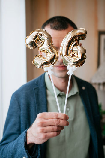 Man in a blue jacket holds in his hands little foiled gold balloons of the number 36 on sticks