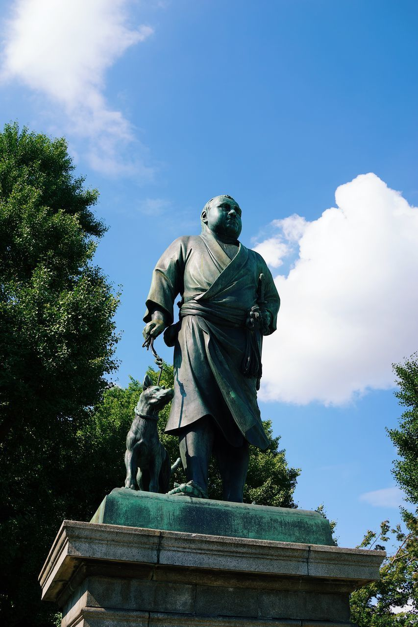 LOW ANGLE VIEW OF STATUE AGAINST BLUE SKY AND TREES