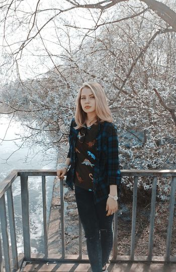 Portrait of young woman standing on bridge against bare trees