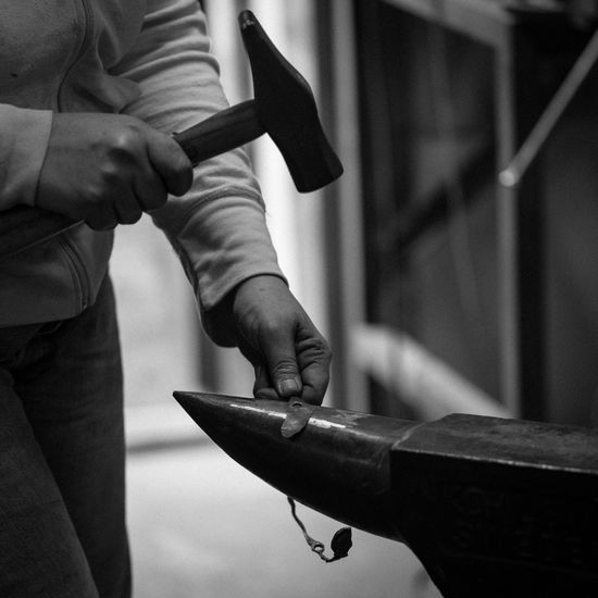 Midsection of blacksmith working on metal at workshop