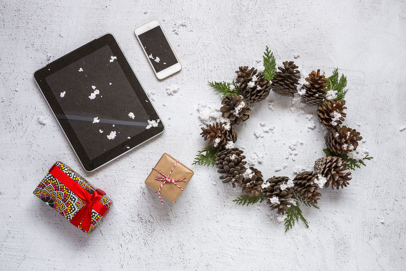 High angle view of christmas decoration and digital tablet by smart phone on table