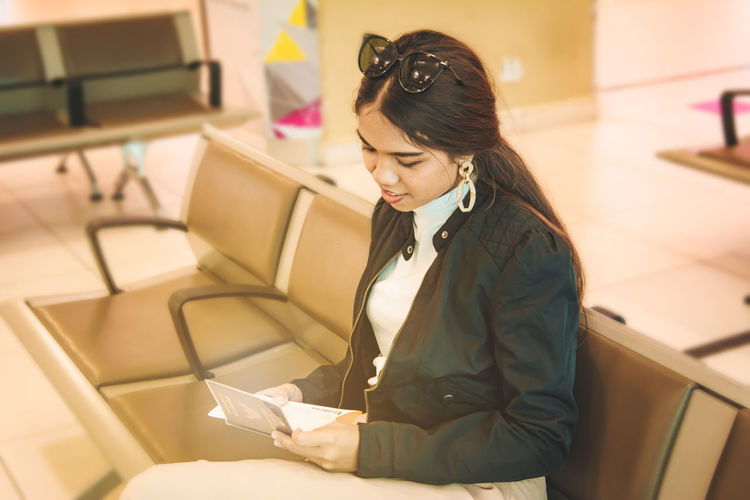 Young woman holding passport while sitting in airport