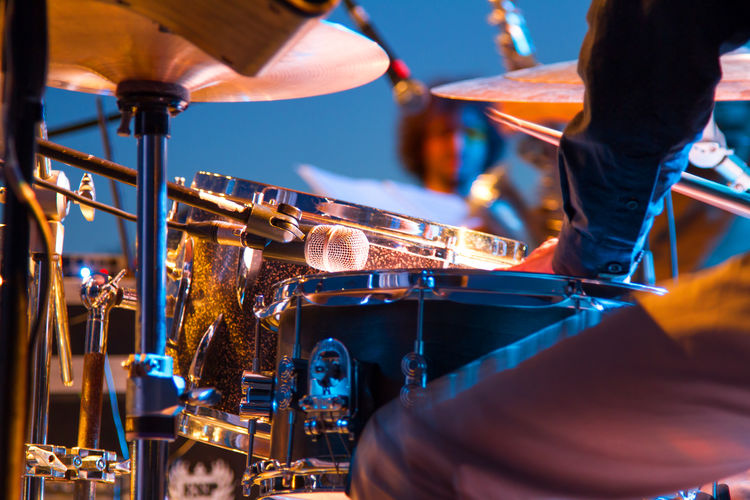 Close-Up Of Drummer With Drum Kit On Illuminated Stage