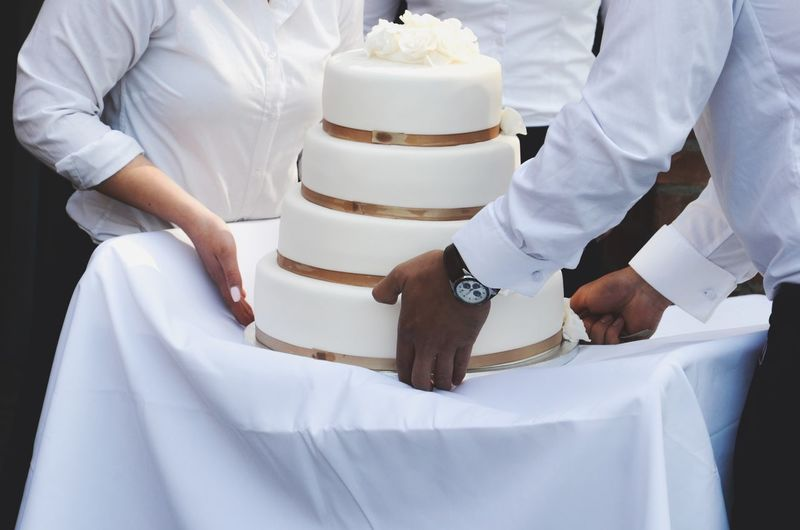 Midsection Of Waiters Placing Wedding Cake On Table In Ceremony