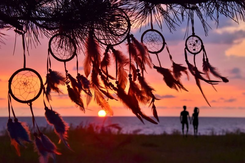 Close-up of dreamcatchers with couple in background at beach
