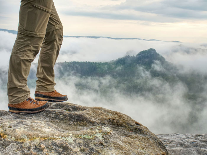 Traveler or hiker legs in sports wearing. view over verdant valley, low clouds.