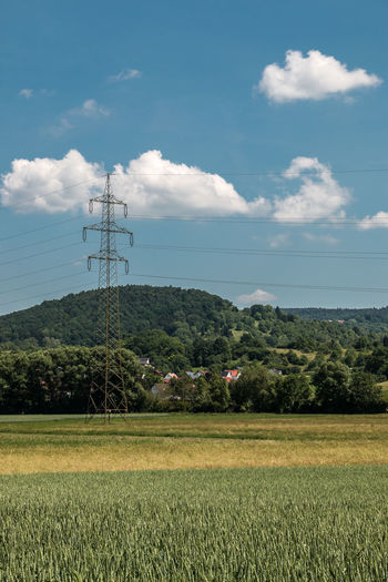 Power pylon in the German countryside with forests, fields and meadows Agriculture Cable Cloud - Sky Connection Day Electricity  Electricity Pylon Environment Field Fuel And Power Generation Growth Land Landscape Nature No People Outdoors Plant Power Line  Power Supply Rural Scene Scenics - Nature Sky Technology