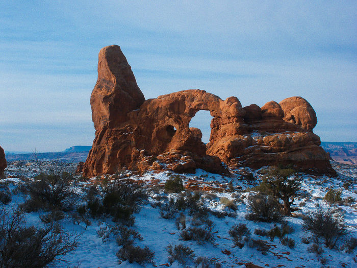 Rock formation at arches national park against sky during winter