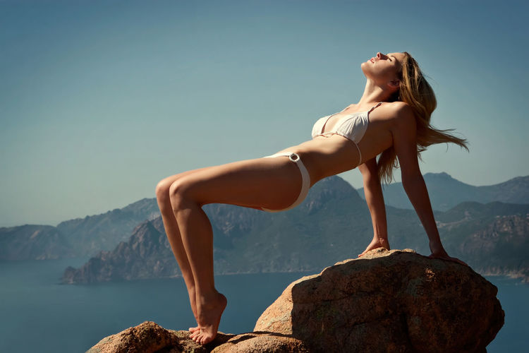 Full Length Of Sensuous Woman In Bikini Balancing On Rock Against Sea And Mountains