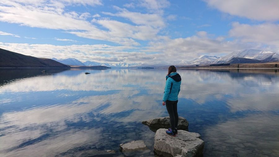 Full length of woman standing by lake against cloudy sky during winter