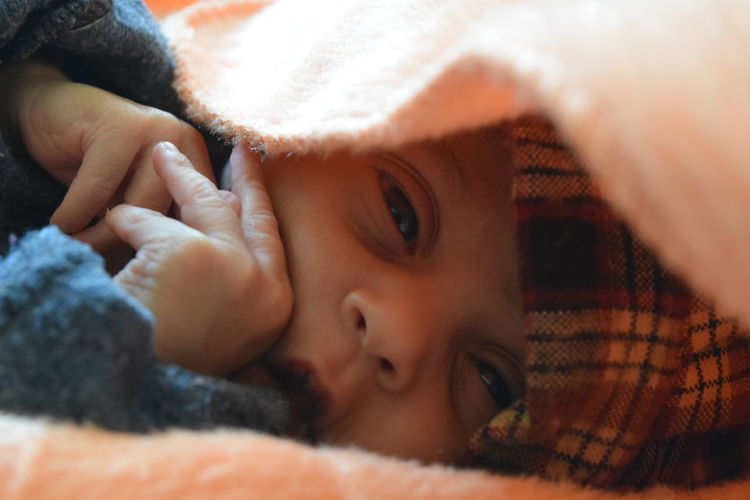 Close-up of newborn baby girl wrapped in blanket