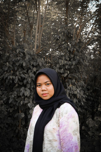 Portrait of a beautiful young woman standing against trees