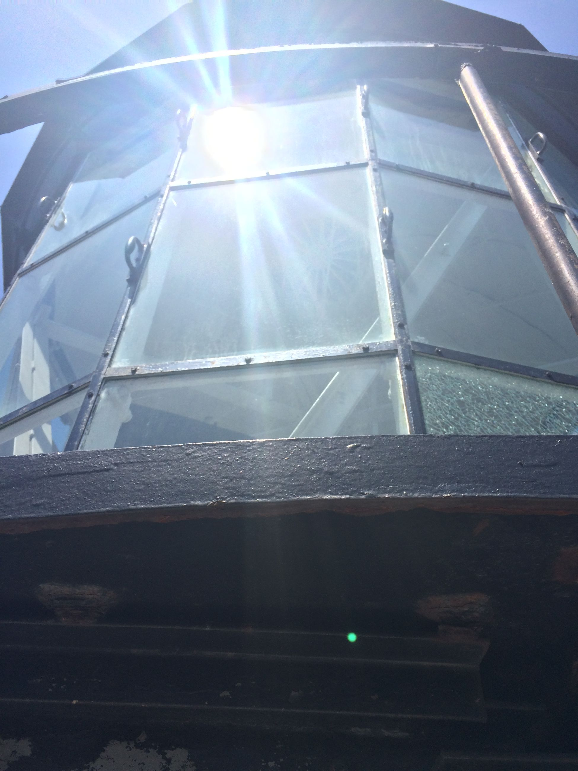 low angle view, sunlight, built structure, architecture, sunbeam, sun, glass - material, sky, lens flare, day, no people, building exterior, modern, window, sunny, reflection, outdoors, metal, clear sky, hanging
