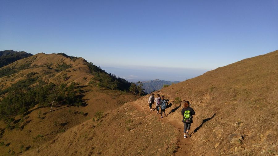 Rear View Of Hikers On Mountain Against Clear Sky