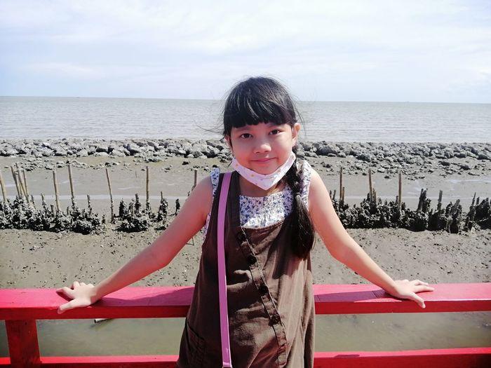 Portrait of girl on beach against sky