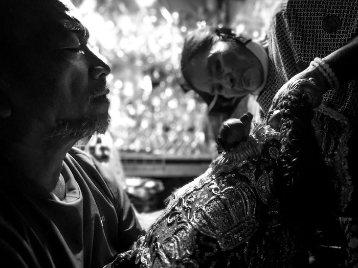 A couple working together in removing the old clothing of the image of Sr. Sto. Niño in a stall beside the Basilica. The husband continues to repair for a living regardless of its limitations due to amputated arm Philippines Sinulog The Portraitist - 2018 EyeEm Awards Bonding Emotion Love Men People Real People Togetherness The Photojournalist - 2018 EyeEm Awards