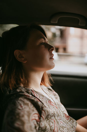 Portrait of beautiful young woman with dark short hair and silver earrings sitting in the car window