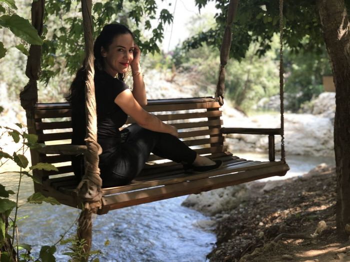 Portrait of smiling woman sitting on swing in forest