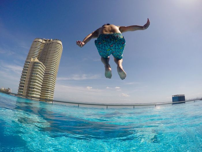 Full length of shirtless man jumping in infinity pool
