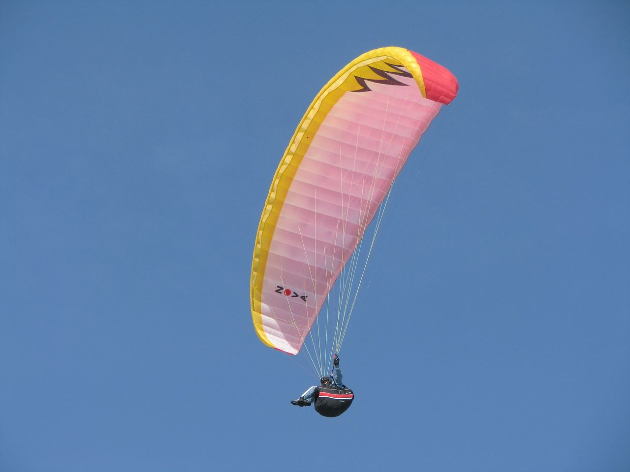 extreme sports, parachute, mid-air, flying, leisure activity, adventure, paragliding, low angle view, real people, lifestyles, skydiving, outdoors, day, blue, clear sky, sport, one person, nature, sky, people