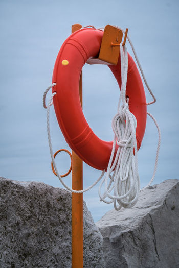 Drowning Hanging Lakefront Life Saver Post Red Rock Beauty In Nature Beauty In Nature Blue Sky Close-up Day Lakeshore Life Belt Nature No People Outdoors Prevention Red Rope Safety Sea Sky Water Waterfront