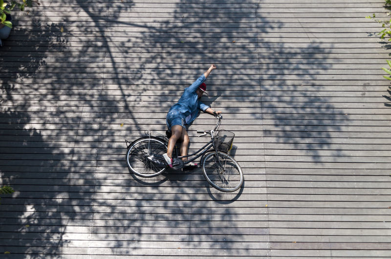 High angle view of woman with bicycle lying down on wooden walkway