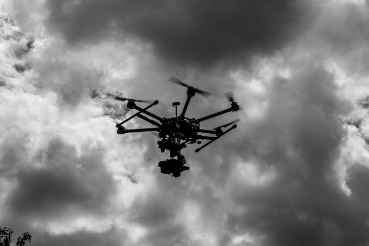 Low Angle View Of Drone Against Cloudy Sky
