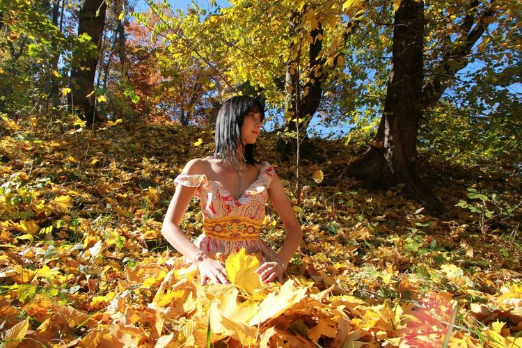 Full length of a woman staying on leaves during autumn