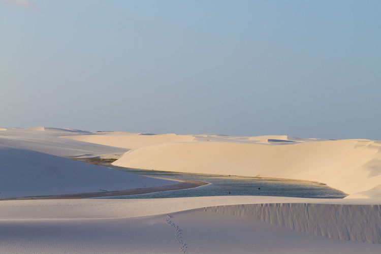 Scenic view of desert against clear sky during winter