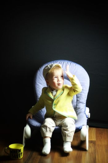 Cute boy sitting on hardwood floor