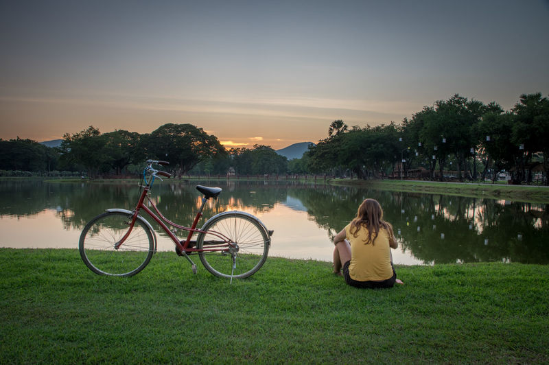 Ancient temples in sukhothai Buddha Buddhist Temple Water Plant Grass Lake Sky Bicycle Transportation Nature Tree Leisure Activity Lifestyles Beauty In Nature Real People Women Scenics - Nature Sitting Mode Of Transportation Sunset Non-urban Scene Outdoors