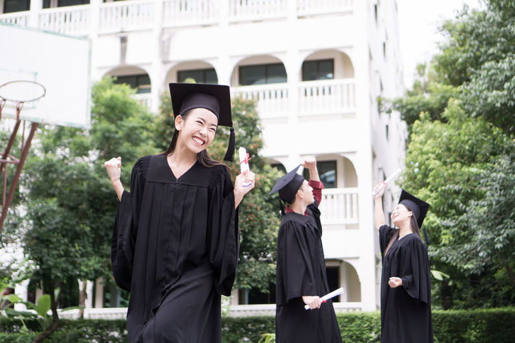 Cheerful Student With Clenched Fist Wearing Graduation Gown