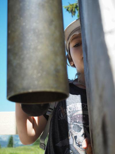 Boy Hiding Behind Hanging Metallic Pipes