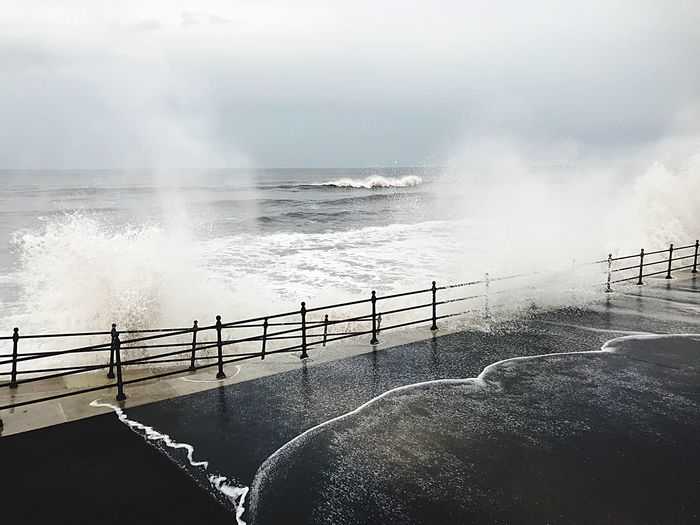 Anger of the waves Water Sea Railing Sky Nature Beauty In Nature Motion Day Horizon Over Water Power In Nature Outdoors Power Scenics - Nature Horizon Wave Two People People Men Breaking Hitting