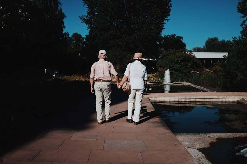 Men standing by swimming pool against trees