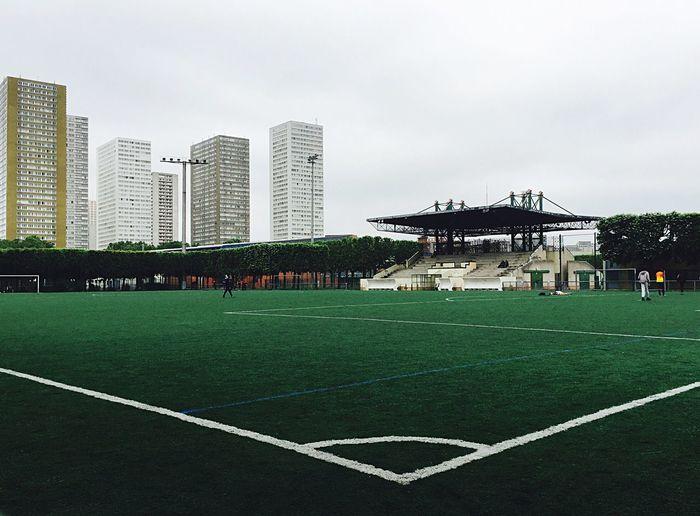 Football ground against tall buildings