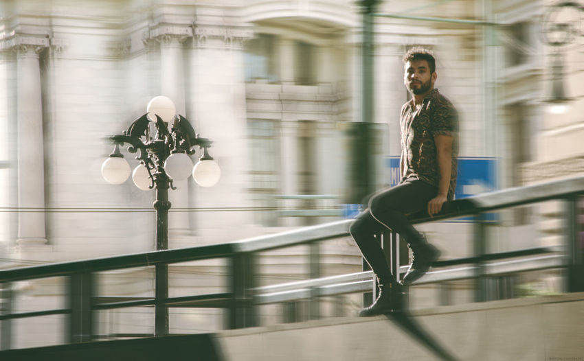 Blurred motion of man sitting on railing by road in city