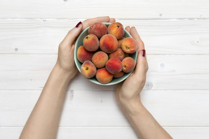 Female hands holding a bowl of peaches Fresh Fruit Bowl Bowl Of Fruit Apple - Fruit Bowl Of Peaches Female Hands Female Hands Holding Flatlay Food Food And Drink Freshness Fruit Hand Healthy Eating Healthy Lifestyle High Angle View Holding Human Hand Organic Peaches Ripe Table