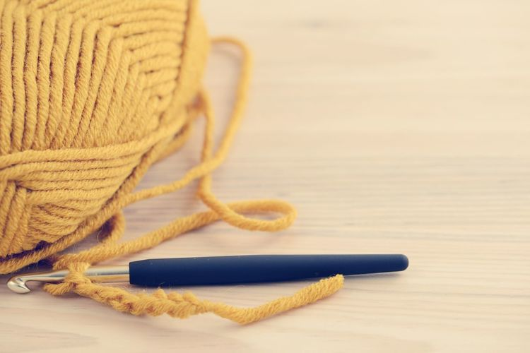 Close-Up Of Knitting Needle And Wool On Wooden Table