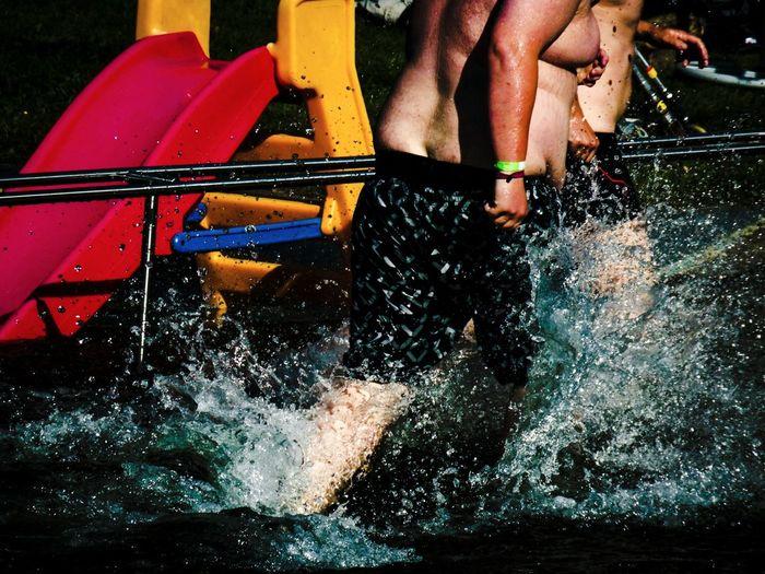 Shirtless men splashing water at park