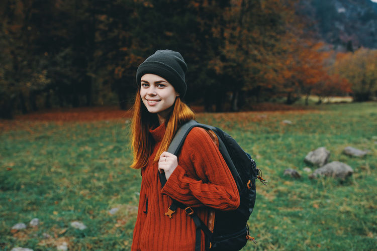 Portrait of smiling young woman standing on field during autumn