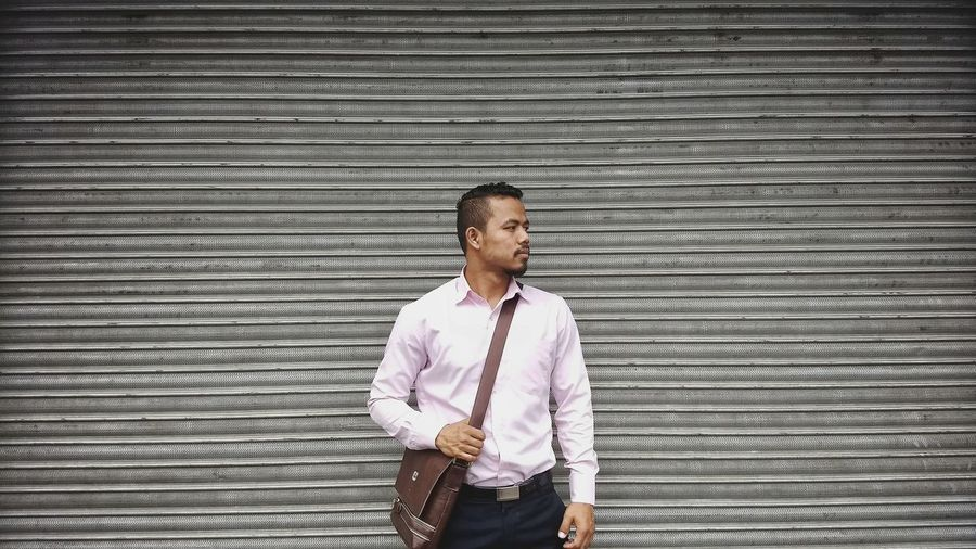 Businessman looking away while standing against closed shutter
