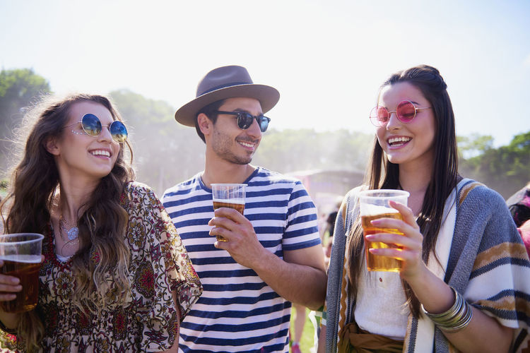 Friends holding drinks while talking in party