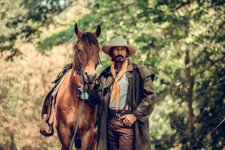 Cowboy with horse standing in forest