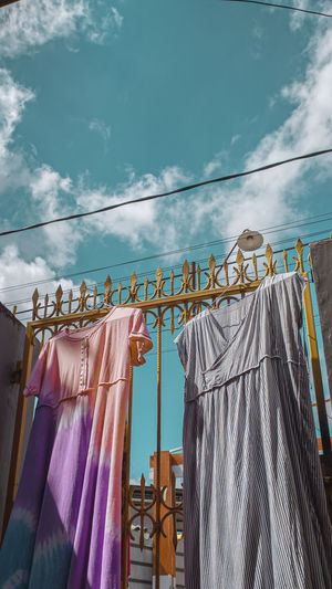 Low angle view of clothes hanging on clothesline against building