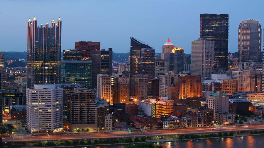 Illuminated Buildings In City Against Sky