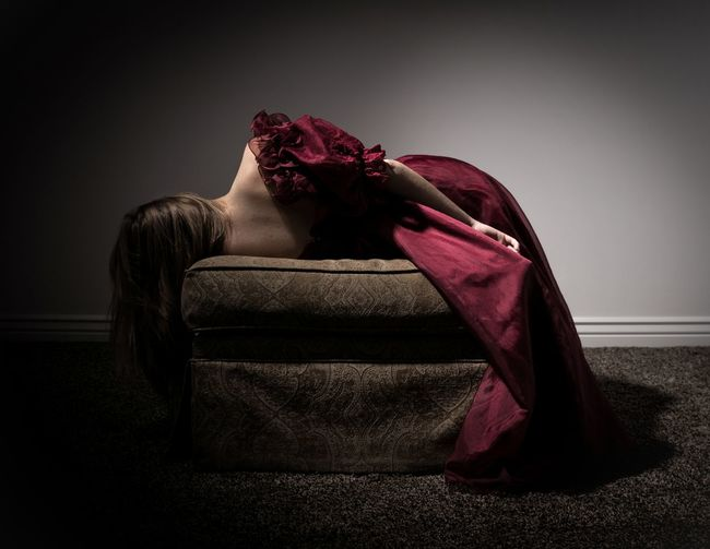 Rear view of woman lying on ottoman against wall